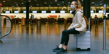 Young woman in face mask at airport