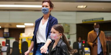 Mother & daughter wearing face masks in train station